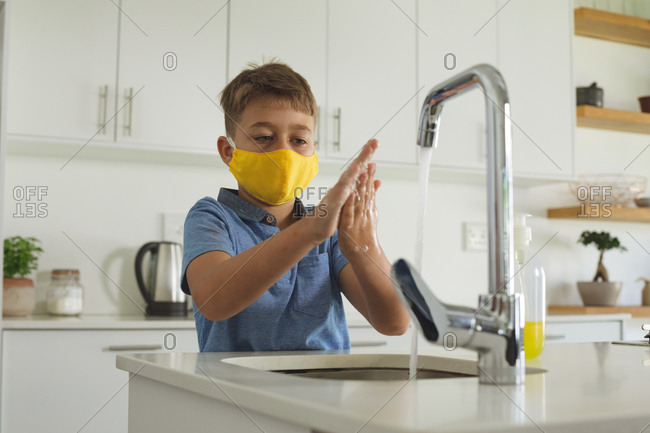 Caucasian boy spending time at home, in kitchen washing his hands wearing yellow face mask. Social distancing during Covid 19 Coronavirus quarantine lockdown.