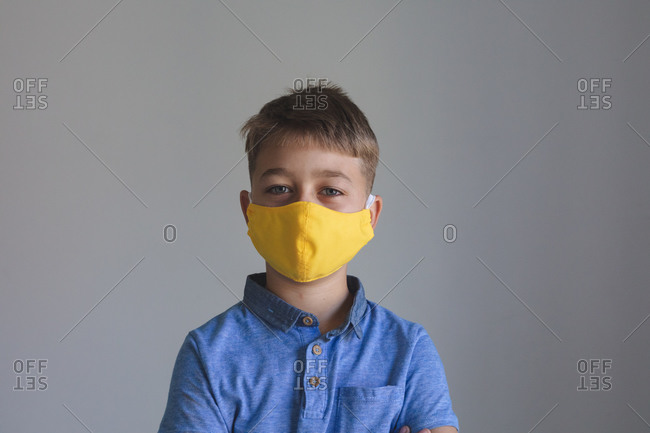 Portrait of Caucasian boy spending time at home, wearing yellow face mask looking at camera on grey background. Social distancing during Covid 19 Coronavirus quarantine lockdown.