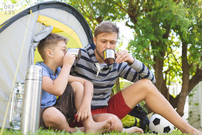 Caucasian man spending time with his son together, camping in garden, sitting in tent, drinking tea. Social distancing during Covid 19 Coronavirus quarantine lockdown.