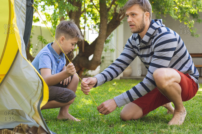 Caucasian man spending time with his son together, camping in garden, putting tent up. Social distancing during Covid 19 Coronavirus quarantine lockdown.