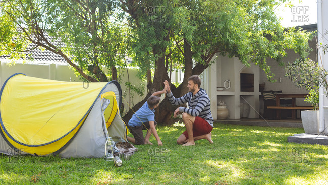 Caucasian man spending time with his son together, camping in garden, sitting by tent, high fiving. Social distancing during Covid 19 Coronavirus quarantine lockdown.