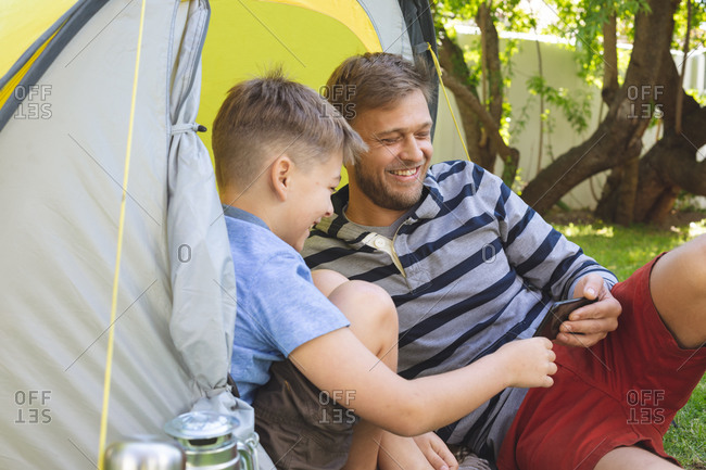 Caucasian man spending time with his son together, camping in garden, lying in tent using smartphone, smiling. Social distancing during Covid 19 Coronavirus quarantine lockdown.