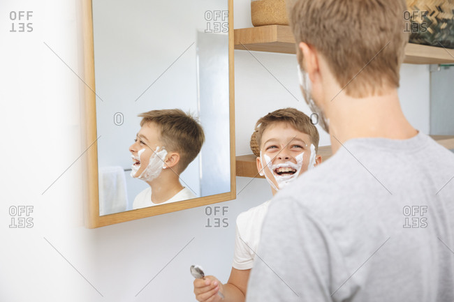 Caucasian man at home with his son together, in bathroom, shaving with shaving cream on faces, smiling. Social distancing during Covid 19 Coronavirus quarantine lockdown.