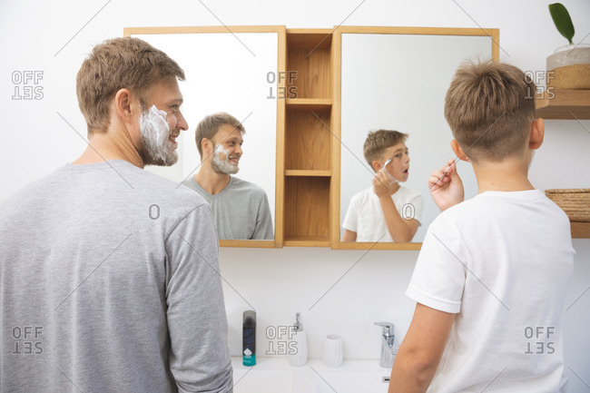 Caucasian man at home with his son together, in bathroom, shaving with shaving cream on faces, looking at mirror. Social distancing during Covid 19 Coronavirus quarantine lockdown.