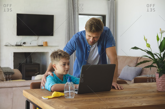 Caucasian man at home with his son together, boy sitting at table, using laptop computer, father standing next to him. Social distancing during Covid 19 Coronavirus quarantine lockdown.