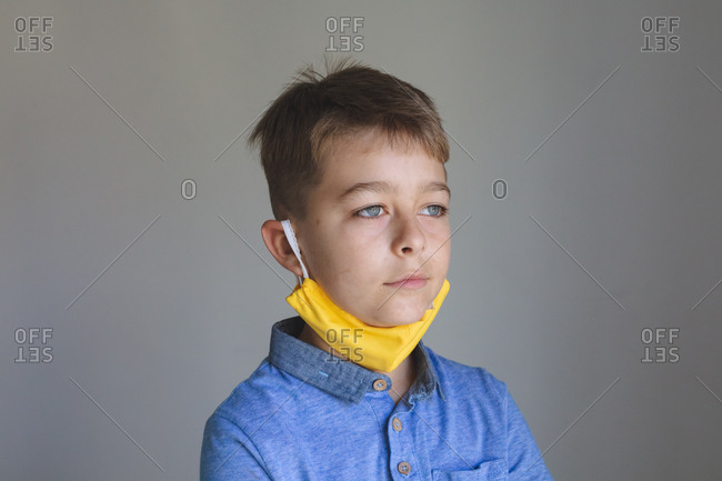 Side view of Caucasian boy spending time at home, wearing yellow face mask looking at camera on grey background. Social distancing during Covid 19 Coronavirus quarantine lockdown.
