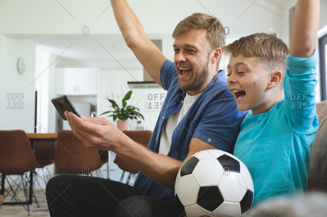 Caucasian man at home with his son together, sitting on sofa in living room, watching sports football game on smartphone, cheering. Social distancing during Covid 19 Coronavirus quarantine lockdown.