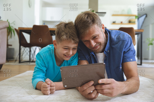 Caucasian man at home with his son together, lying on rug in living room, using digital tablet, smiling. Social distancing during Covid 19 Coronavirus quarantine lockdown.
