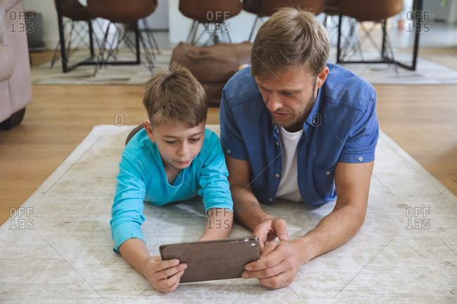 Caucasian man at home with his son together, lying on rug in living room, using digital tablet. Social distancing during Covid 19 Coronavirus quarantine lockdown.