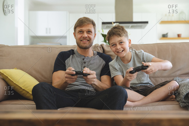 Caucasian man at home with his son together, sitting on sofa in living room, playing video games, smiling. Social distancing during Covid 19 Coronavirus quarantine lockdown.