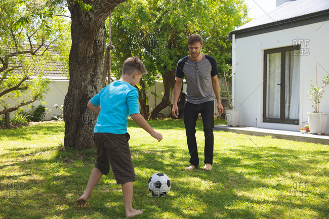 Caucasian man spending time with his son together, playing football in garden. Social distancing during Covid 19 Coronavirus quarantine lockdown.