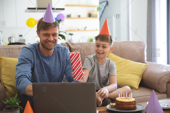 Caucasian man spending time at home with his son together, having birthday party using laptop computer for video chat. Social distancing during Covid 19 Coronavirus quarantine lockdown.