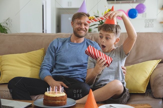 Caucasian man spending time at home with his son together, wearing party hats boy receiving birthday present. Social distancing during Covid 19 Coronavirus quarantine lockdown.