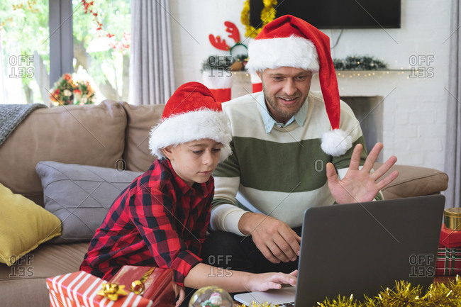 Caucasian man at home with his son at Christmas, wearing Santa hats sitting in living room using laptop for video call. Social distancing during Covid 19 Coronavirus quarantine lockdown.