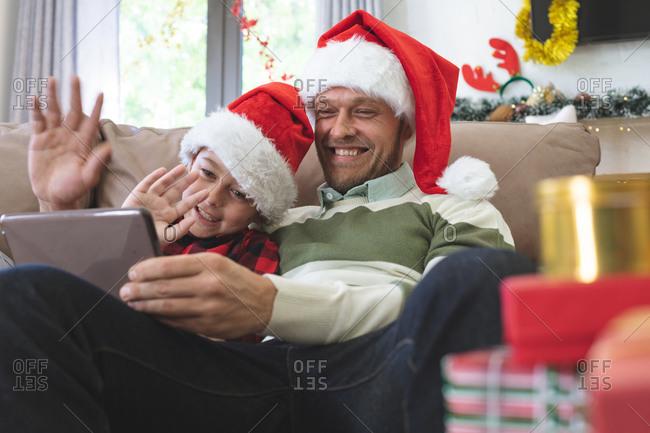 Caucasian man at home with his son at Christmas, wearing Santa hats sitting on sofa in living room, using digital tablet, waving. Social distancing during Covid 19 Coronavirus quarantine lockdown.