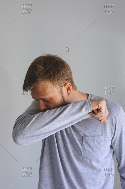 Caucasian man spending time at home, being sick, coughing sneezing, covering his face with elbow on grey background. Social distancing during Covid 19 Coronavirus quarantine lockdown.