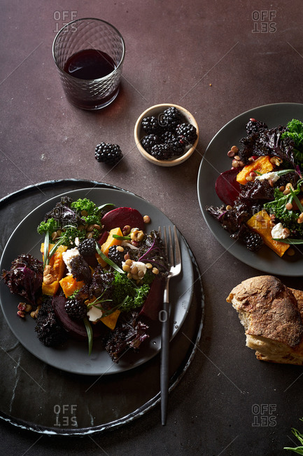 Vegetarian salad with roasted butternut squash, kale, beetroot and blackberries garnished with tarragon leaves.