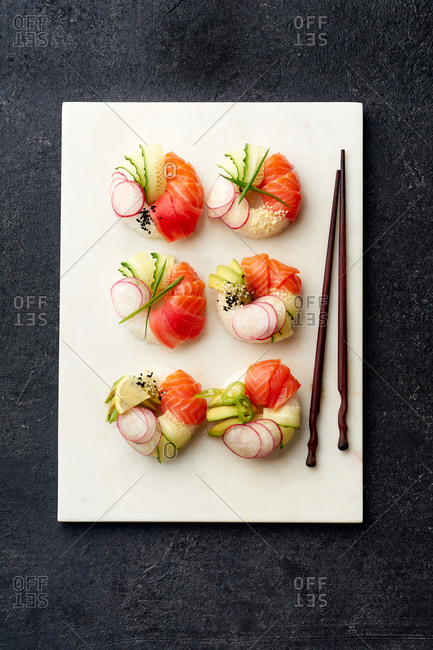 Top view of sushi donuts with salmon and veggies on dark background