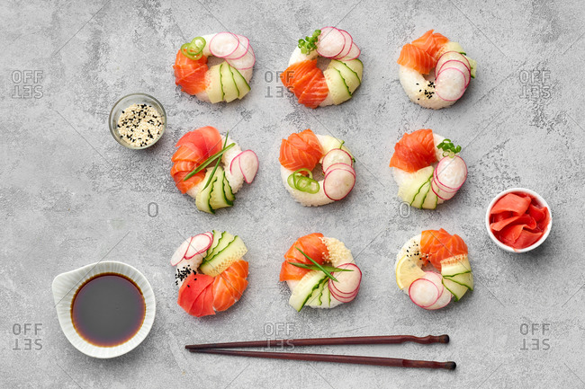 Top view of sushi donuts with salmon and veggies on gray background