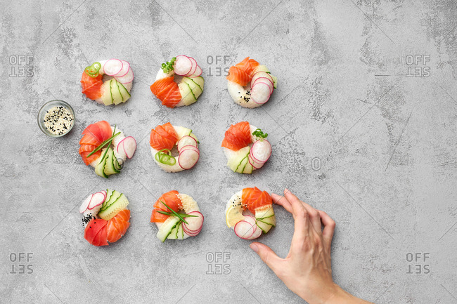 Female hand taking one of the sushi donuts with salmon and veggies