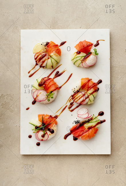 Overhead image of sushi donuts with salmon and veggies on beige background topped with sauce