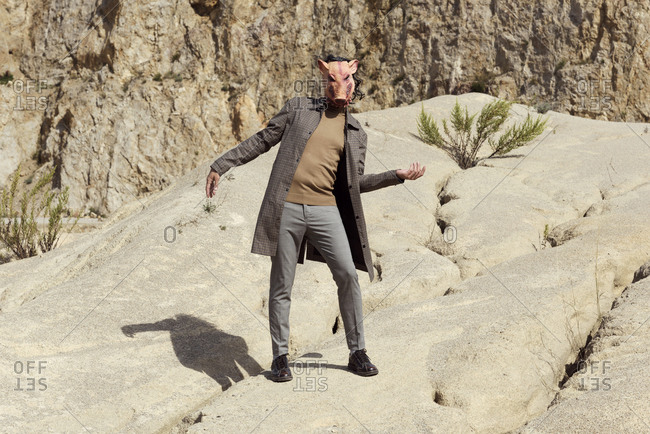 Young man wearing a plaid coat, trousers, brown polo neck and a disturbing pig mask while posing in an abandoned quarry