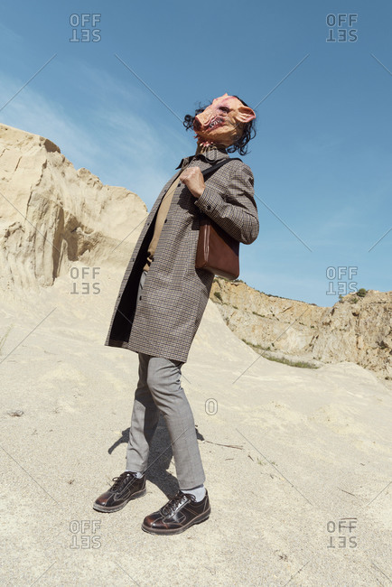 Man wearing a plaid coat, trousers, brown polo neck and a disturbing pig mask while posing in an abandoned quarry