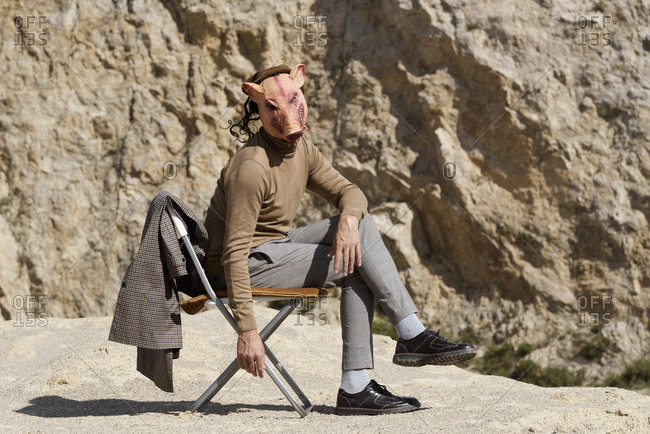 Young man wearing a plaid coat, trousers, brown polo neck and a disturbing pig mask while sitting on chair in an abandoned quarry
