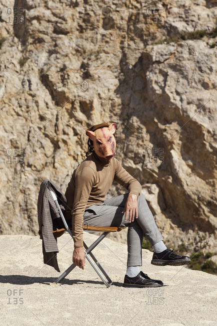 Portrait of a young man wearing a plaid coat, trousers, brown polo neck and a disturbing pig mask while sitting on chair in an abandoned quarry