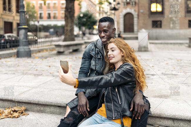 Beautiful multiethnic couple taking selfie in the street
