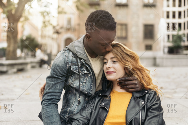 Young Black male kissing his Caucasian girlfriend's forehead in the street