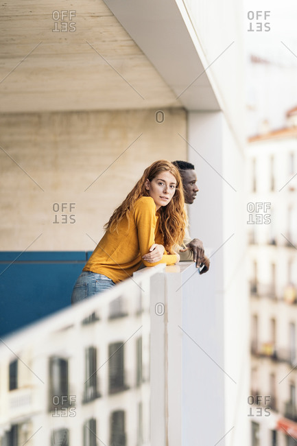Multiethnic couple standing side by side on balcony