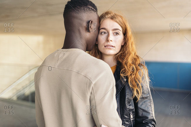 Multi-racial young couple hugging each other