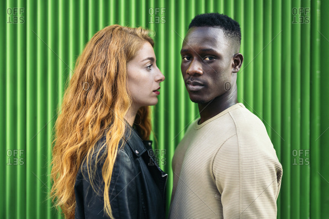 Redhead woman and African American man standing face to face against green background