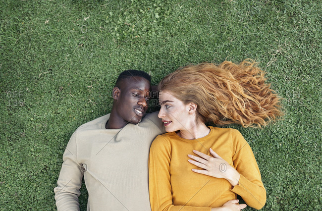 Lovely young couple looking at each other while lying in the grass