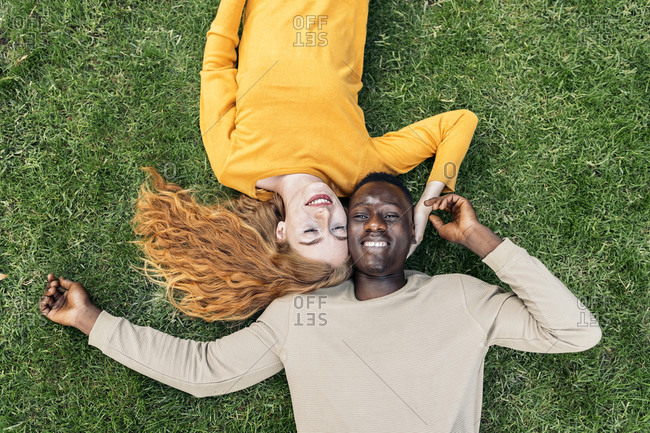 Lovely young couple lying in the grass viewed from above