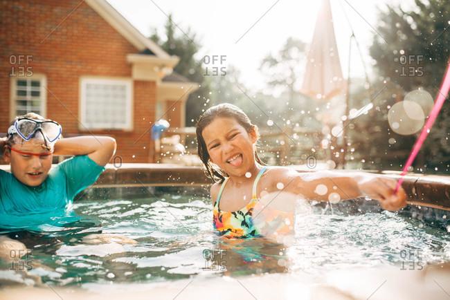 Children splashing around in a backyard hot tub