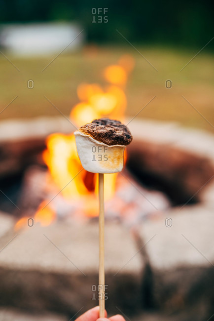 Close up of a roasted marshmallow in front of fire pit