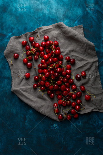 Overhead view of cherry on linen on dark surface