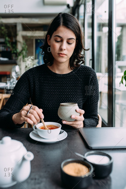 Young beautiful woman drinking tea in restaurant