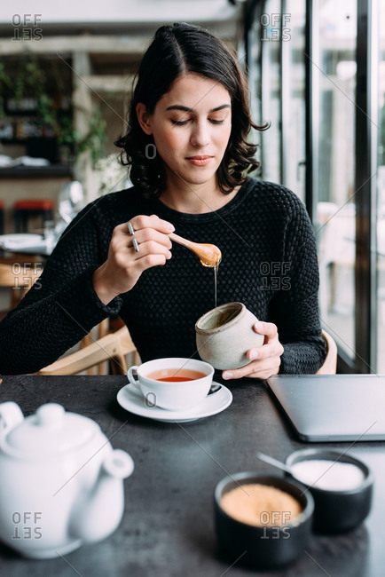 Young beautiful woman adding honey to her tea in restaurant