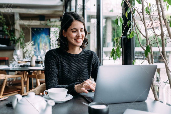 Happy young businesswoman working on her lap top in a restaurant