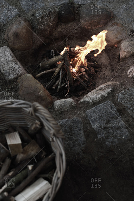 Overhead view of a basket filled with wood beside a bonfire