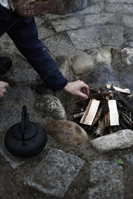 Man preparing sticks in a firepit for preparing tea