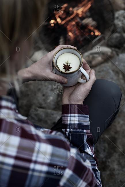 Man drinking apple tea outside by bon fire