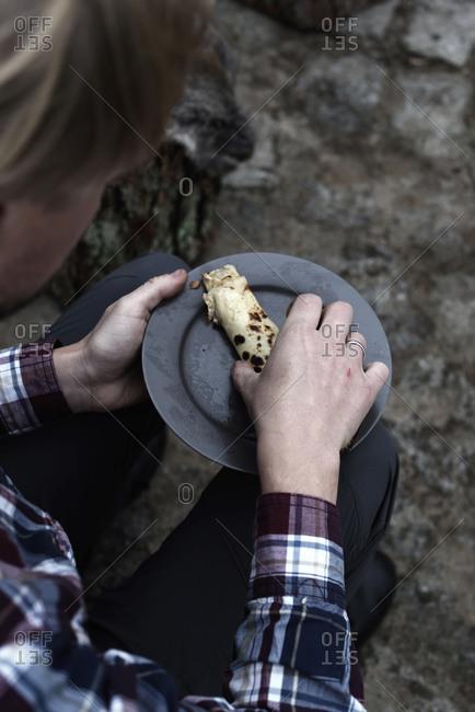 Man eating pancake made over campfire outdoors
