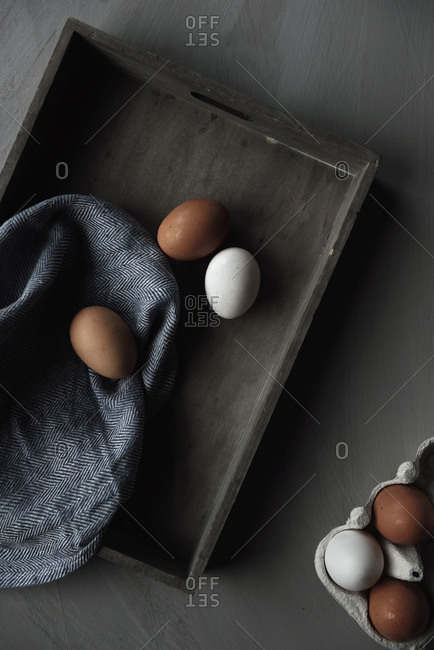Brown and white eggs on a wooden tray
