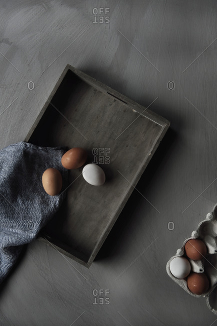 Brown and white eggs on a wooden tray on gray background