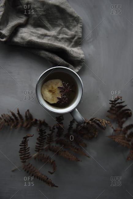 Apple tea in mug on grey table