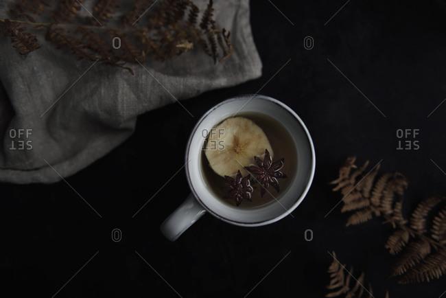 Apple tea in mug on black table